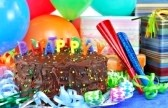 6827599-happy-birthday-candles-on-top-of-a-chocolate-birthday-cake--colorful-balloons-party-horns-and-gifts-